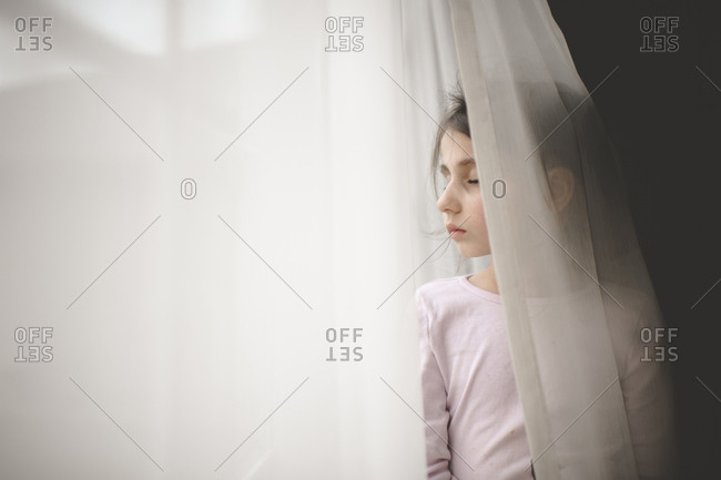 Girl with eyes closed standing by window curtain at home