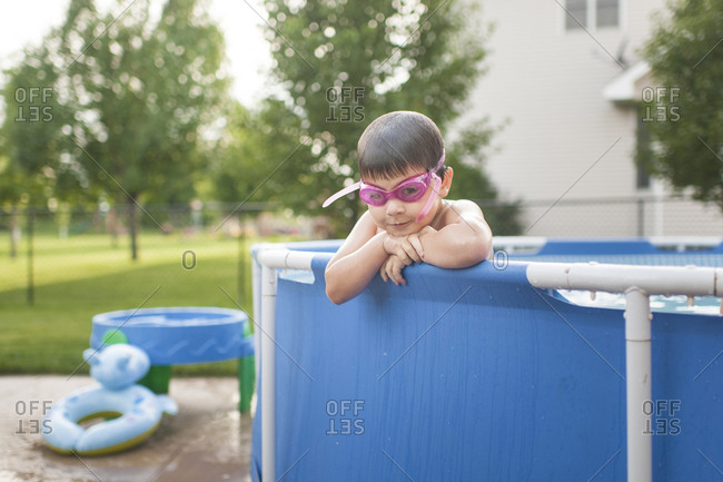 Portrait of boy wearing swimming goggles in wading pool