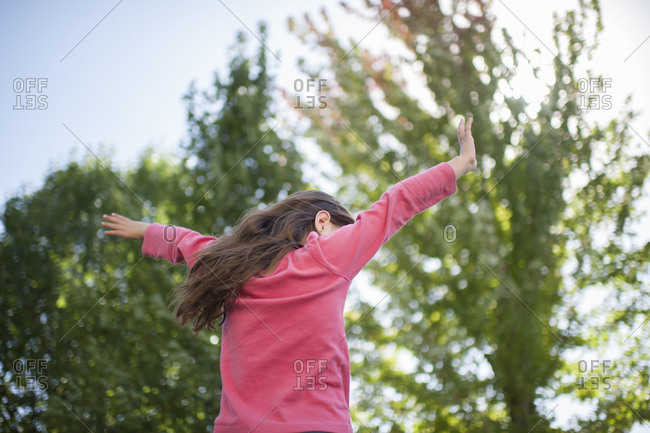 Low angle view of playful girl with arms outstretched by trees in garden