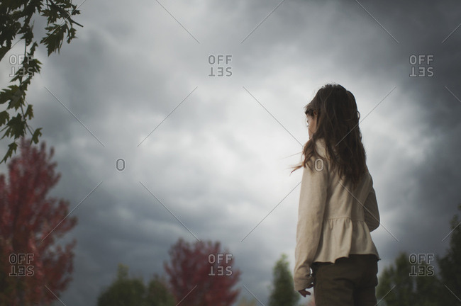 Side view of girl standing against cloudy sky