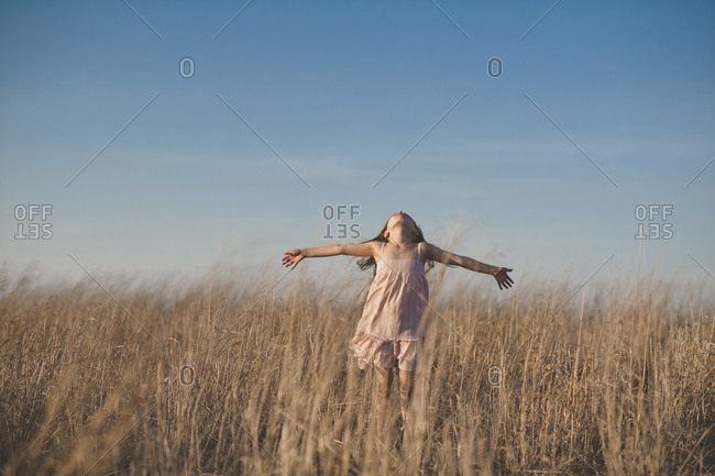 Happy girl with arms outstretched standing on dry grassy field against blue sky