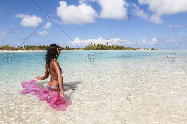 Woman with sarong sitting in lagoon against sky