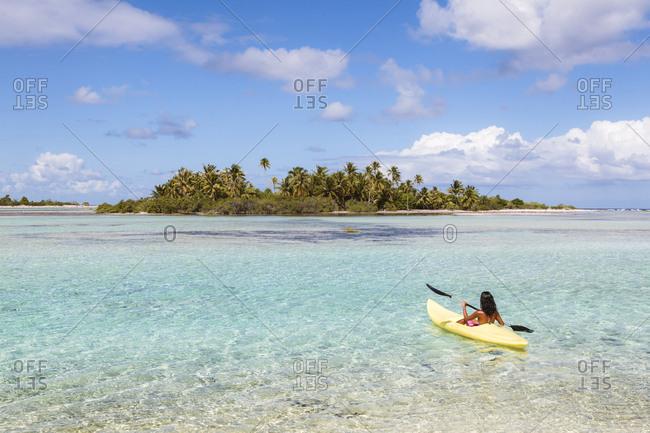 Woman kayaking in lagoon against sky
