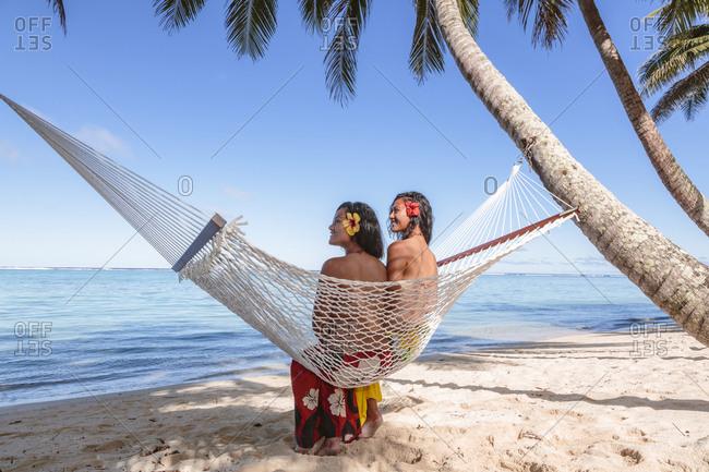Female friends relaxing on hammock at beach against blue sky