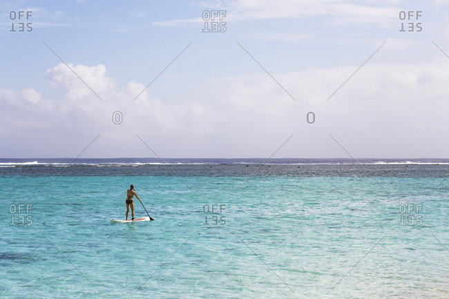 Rear view of woman paddle boarding in lagoon against sky