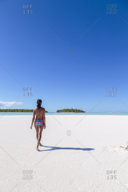 Rear view of woman walking on sand at beach against blue sky during sunny day
