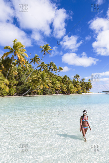 Woman wearing snorkel walking at beach against sky