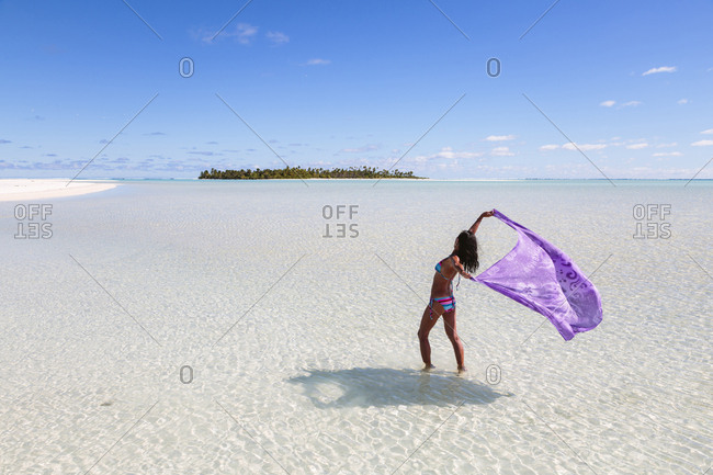 Woman holding sarong while standing in Aitutaki lagoon against blue sky