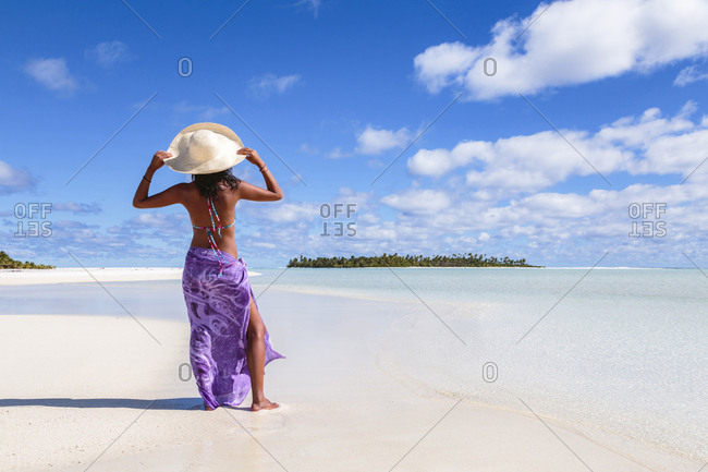 Rear view of woman wearing sun hat standing at beach against sky during sunny day