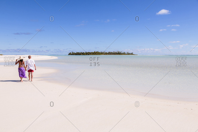 Rear view of couple walking at beach against blue sky during sunny day