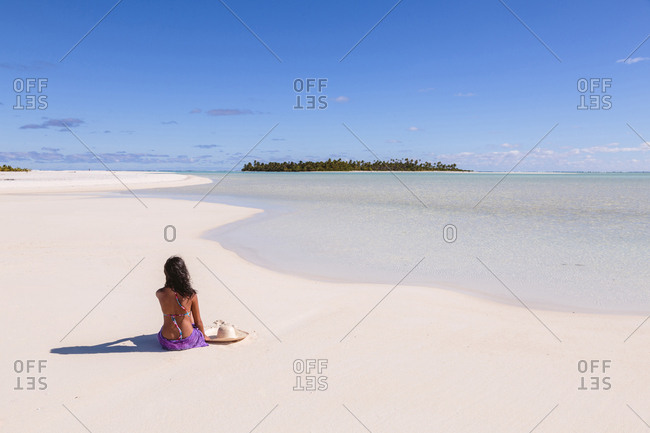Rear view of woman relaxing at beach against blue sky