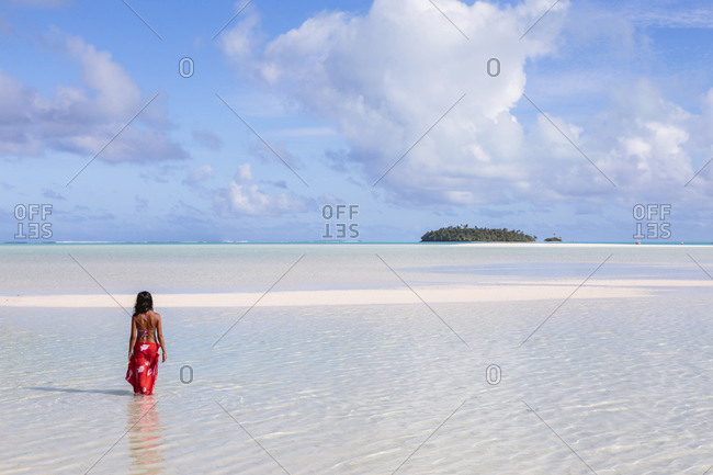 Rear view of woman wearing sharong standing in Aitutaki lagoon against sky
