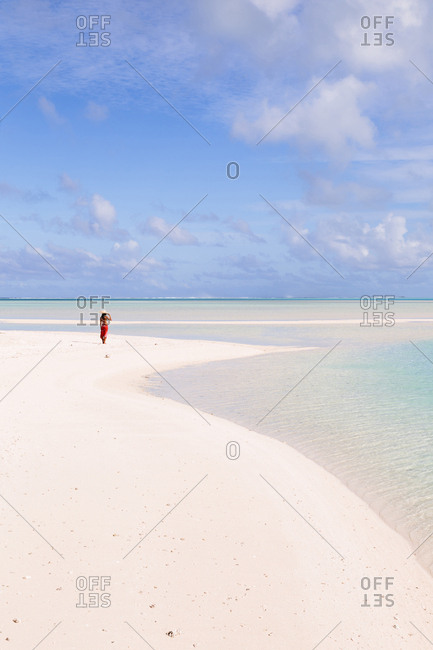 Distant view of woman at beach against sky during sunny day
