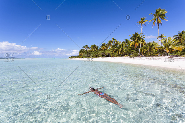 High angle view of woman swimming in Aitutaki lagoon against blue sky