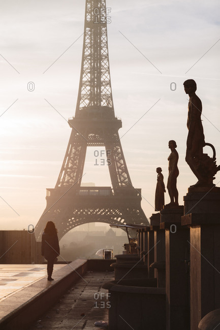 Rear view of silhouette woman looking at Eiffel Tower against sky