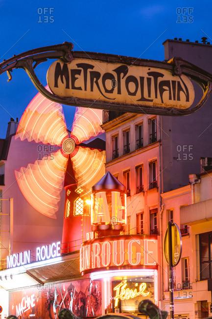 PARIS, FRANCE - NOVEMBER 12 2015: Illuminated windmill on Moulin Rouge against blue sky at dusk