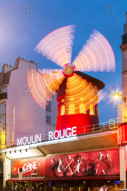 Illuminated windmill on Moulin Rouge against sky at dusk