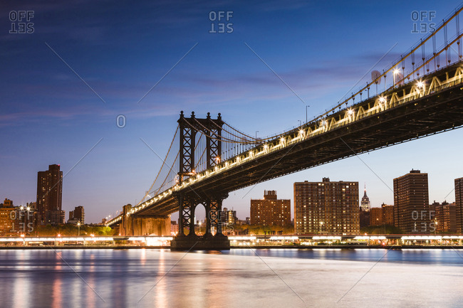 Low angle view of illuminated Manhattan Bridge over East river against blue sky at dusk