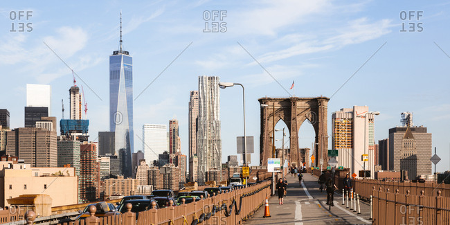 Brooklyn Bridge and One World Trade Center against sky in New York city