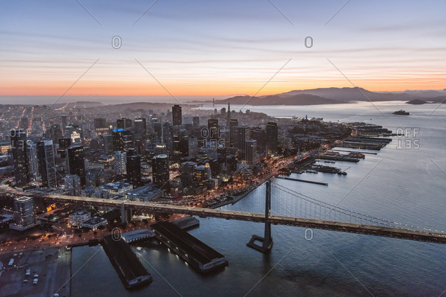 Aerial view of Oakland Bay Bridge over sea by city during sunset