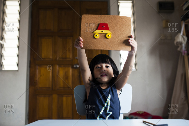 Portrait of cute girl showing craftwork made on cardboard while sitting at table