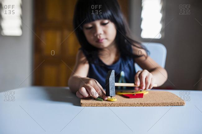 Girl making craftwork on cardboard at home
