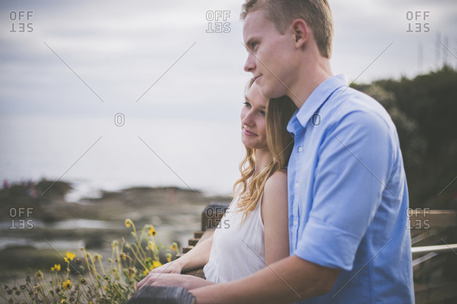 Smiling couple looking away while standing by railing against cloudy sky