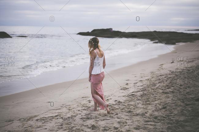 Woman walking at beach against cloudy sky