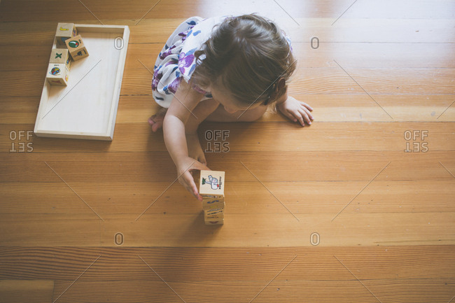 High angle view of girl playing with toy blocks while sitting on floor at home