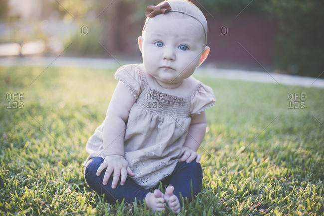 Portrait of cute baby girl sitting on grassy field at backyard