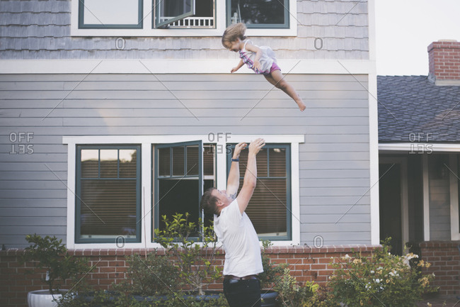 Playful father throwing daughter in air while standing in backyard