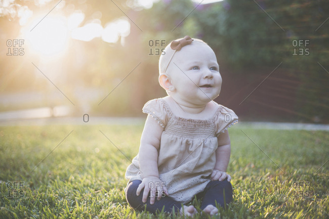 Happy baby girl looking away while sitting on grassy field at backyard