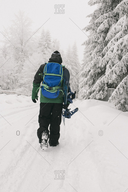 Rear view of man with snowboard walking on snow covered field