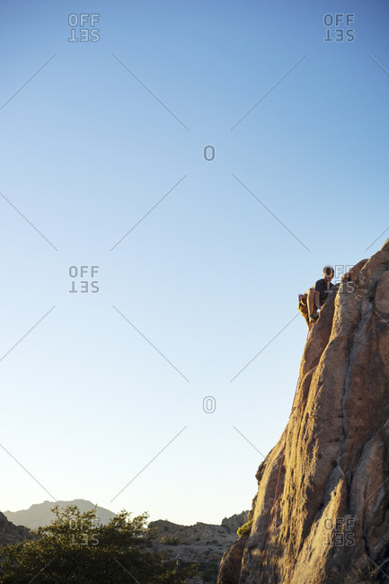 Low angle view of man climbing rock against clear blue sky during sunny day