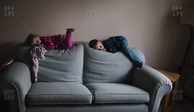Playful siblings lying on sofa at home