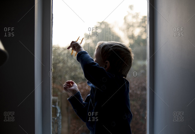 Boy playing with toy while sitting by window at home