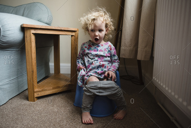 Girl with mouth open sitting on potty in room at home