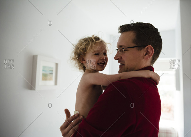 Father carrying happy daughter while standing by wall at home