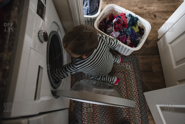 High angle view of boy putting clothes in washing machine at home