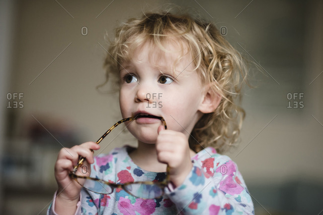 Close-up of girl with eyeglasses in mouth looking away while standing at home