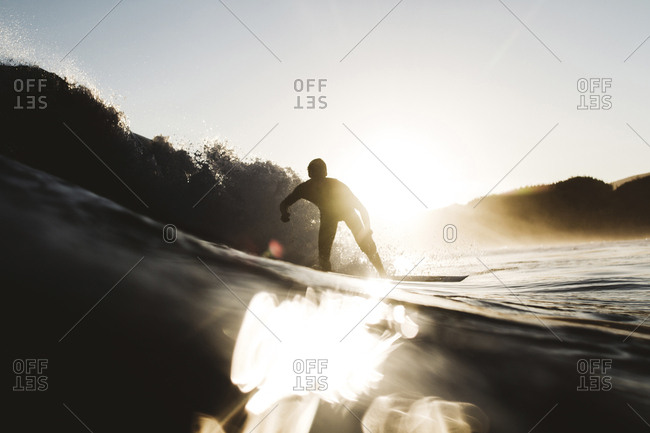 Silhouette man surfboarding on sea against sky during sunset