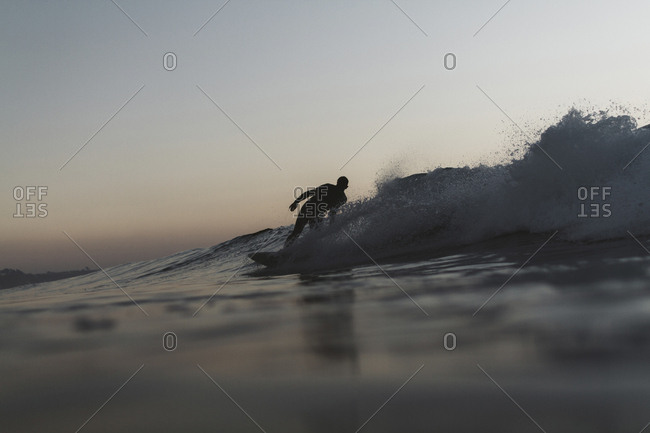 Silhouette man surfboarding on wave in sea against clear sky during sunset