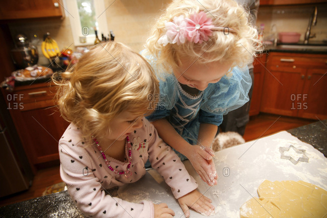 High angle view of happy sisters making cookies in kitchen at home