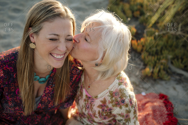High angle view of mother kissing daughter at beach