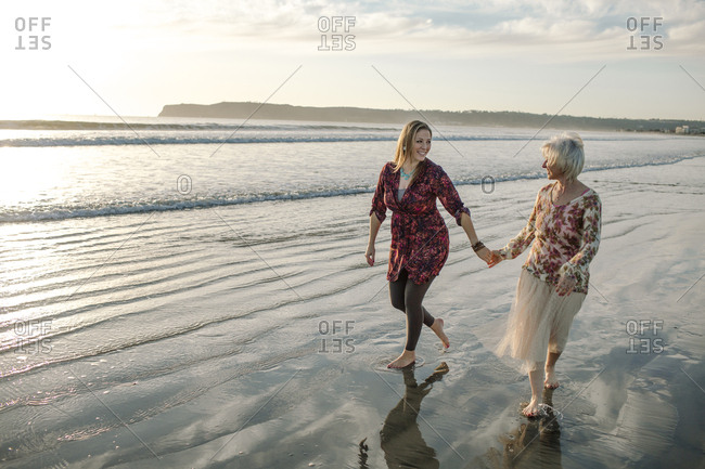 Happy mother and daughter holding hands while walking at beach against cloudy sky
