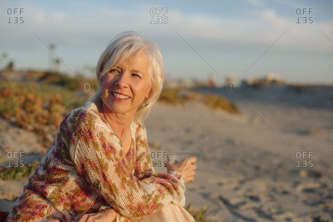 Thoughtful woman with drink sitting at beach during sunset