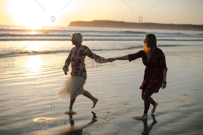 Full length of playful mother and daughter enjoying at beach against sky during sunset