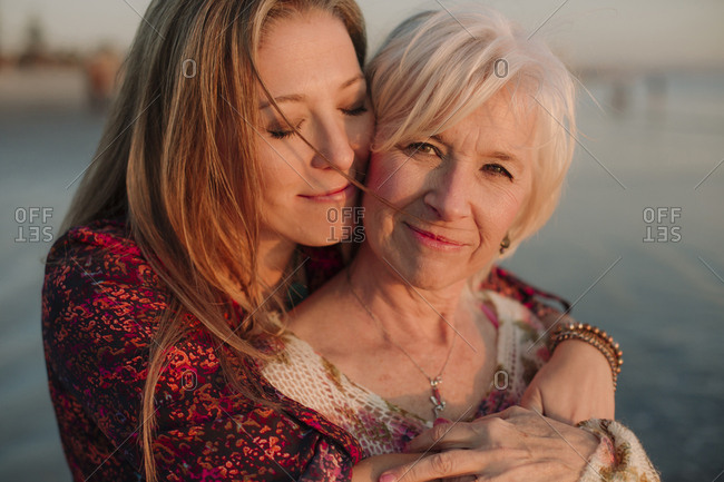 Close-up of mother and daughter embracing at beach during sunset