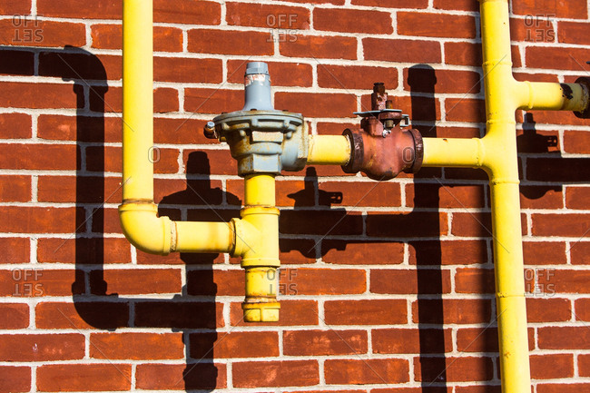 Close up of pipes in front of brick wall