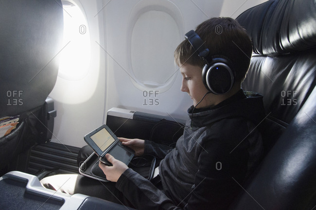 Boy sitting in plane and playing video game